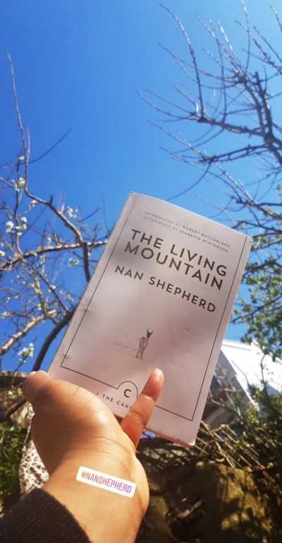 A persons hand holding Nan Shepherds book up to a blue sky